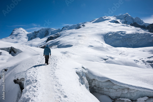 Trekker walking on snow with Mera Peak in background, Nepal