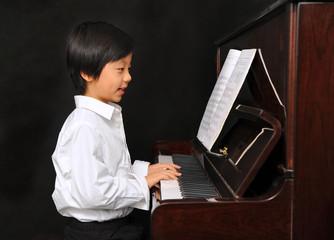 Young Asian boy playing piano