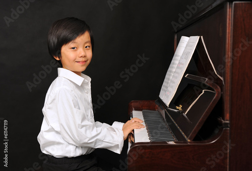 Young Asian boy playing piano (isolated on black background)