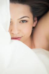Pretty woman under the bedsheet