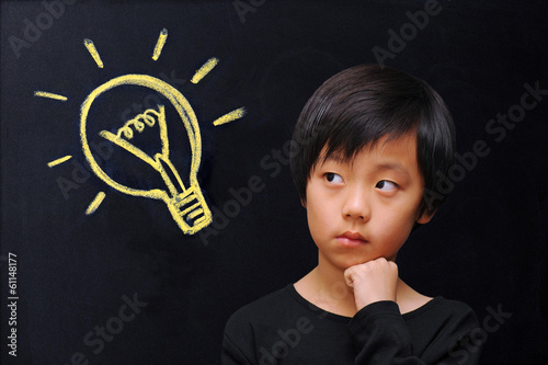 Smart boy in front of blackboard with lightbulb