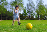 Young Asian boy kicking a yellow ball