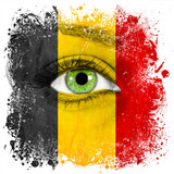 Belgian flag painted on face with green eye showing support