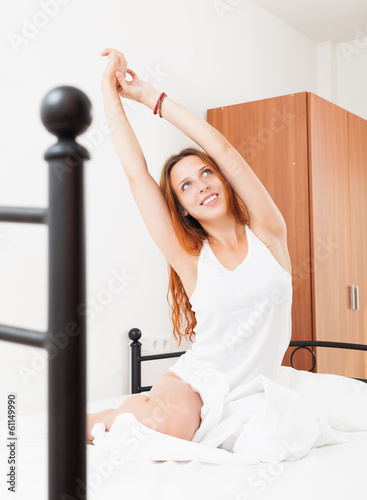 woman waking up in her beautiful bed at home