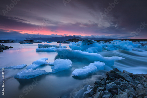 Foto op Canvas Gletsjers Icebergs floating in Jokulsarlon glacier lake at sunset