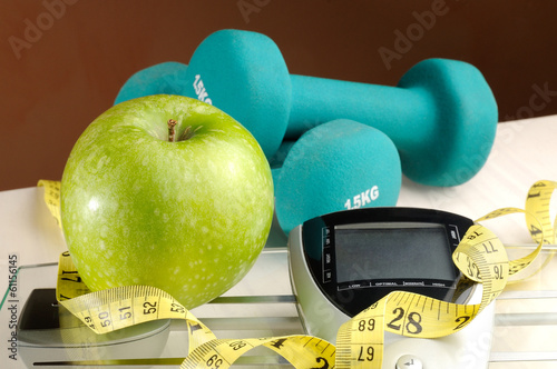 Leinwandbild Motiv healthy apple and sport with brown background