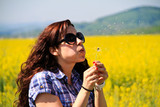 Girl blowing dandelion in rape field