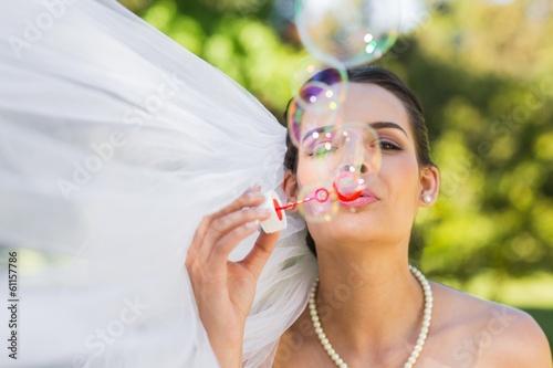 Bride blowing soap bubbles in park