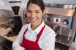 Happy young barista leaning against counter smiling at camera