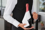 Well dressed waiter holding magnum of champagne