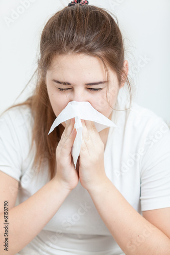 Closeup portrait of sick brunette girl sneezing in paper tissue