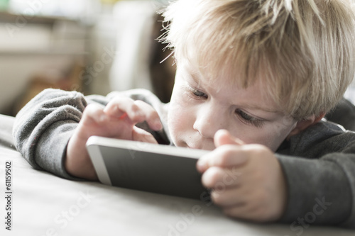 Little boy playing on iPhone 5