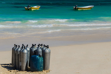 Scuba diving air tanks on sandy Caribbean beach with boats