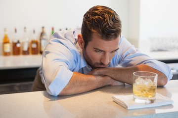 Drunk businessman looking at his whiskey glass after work