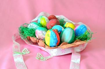 Von Kindern bemalte Ostereier in Eierpappe mit Schleife