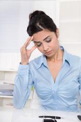 Junge Frau mit Migräne und deprimiert sitzend im Büro