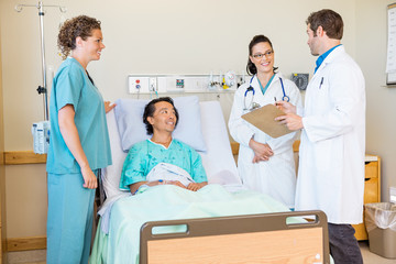 Doctors Discussing Report While Nurse And Patient Looking At The