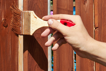 Painting wooden fence with a   brown paint