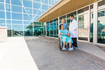 Nurse And Doctor Looking At Patient On Wheelchair At Courtyard