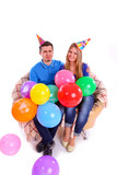 Two friends sitting on the couch with hats and balloons