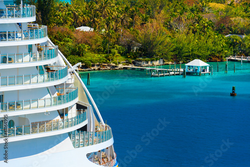 Side of a cruise ship with trees and ocean in background