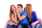 Three friends whispering secrets to shocked brunette at home on