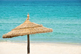 Paraslo exotique en paille, plage et mer