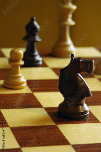 A game of chess, the focus is on the black knight