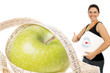 Apfel mit Bandmaß und Frau mit Körperwaage