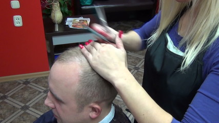 hairdresser cutting  hair with scissors and comb