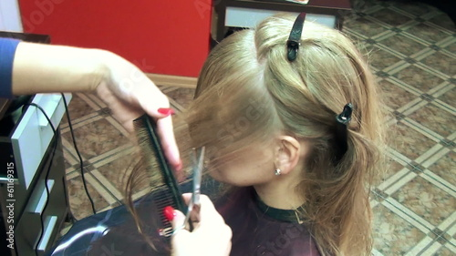 close up of hairdressers hand with comb cutting hair woman
