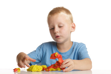 Little boy playing with modeling clay.