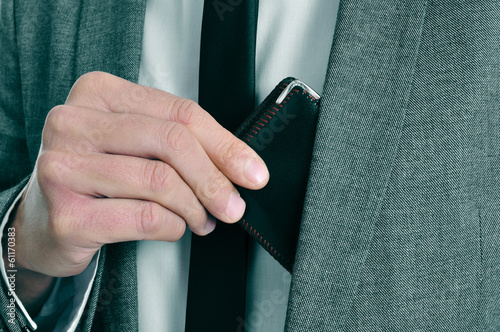man in suit taking out his wallet