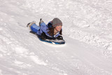 Girl sleds down hill.