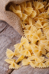 Farfalle pasta dry closeup on an old table. vertical