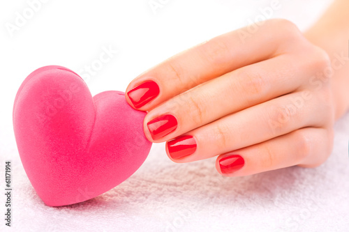 red manicure with gift box on the white towel