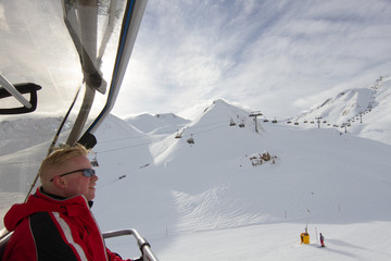 Skier sitting in chair lift