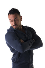 Muscular man with sweatshirt, arms crossed on his chest, looking
