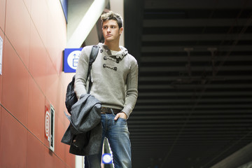 Handsome young man standing in train or subway station