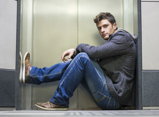 Handsome young man sitting in front of elevator doors