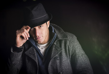 Young man at night, wearing winter coat and fedora hat