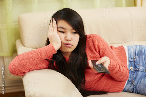 canvas print picture Mädchen zappt gelangweilt mit dem Fernbedienung