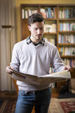 Handsome young man reading newspaper at home
