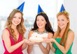 three women wearing hats holding cake with candles