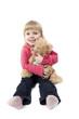 little girl sits with a teddy bear