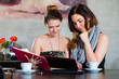 Women in restaurant choosing foor in menu