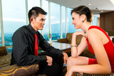 Chinese couple flirting in a luxury sky hotel bar