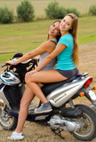 Two beautiful girls enjoying motorcycle ride at countryside