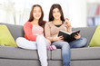 Two teenage girls posing seated on couch, indoors