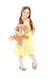 Cute little girl in yellow dress holding a teddy bear